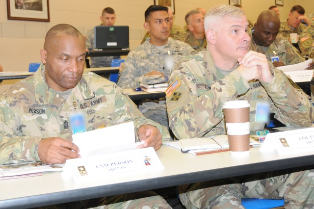 Command Sgt. Maj. Audie Person and Col. John Foley, both of the 188th Infantry Brigade, listen to opening remarks during the First Army Spring Commanders Conference at Fort Leavenworth, Kan.