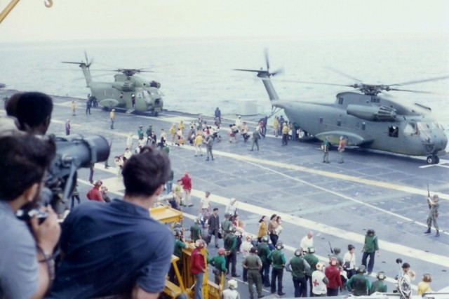 Refugees from South Vietnam debark U.S. Marine Corps Sikorsky CH-53 Sea Stallion helicopters on the flight deck of the U.S. Navy aircraft carrier USS Hancock (CVA-19) during Operation Frequent Wind, before the fall of Saigon, April 29, 1975.