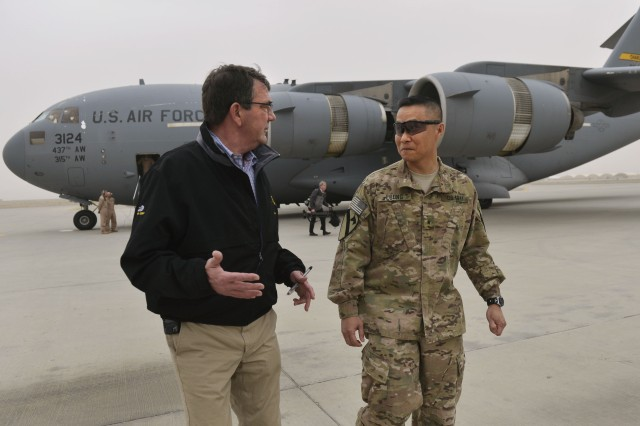 Defense Secretary Ash Carter talks with U.S. Army Brig. Gen. Viet Luong, commander of Train, Advise, Assist Command South, as he arrives on Kandahar Airfield, Afghanistan, Feb. 22, 2014. Carter received updates from leaders and met with service members during his first visit as secretary.