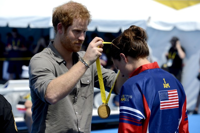 Prince Harry presents a gold medal to U.S. Army Sgt. Elizabeth Marks at the 2016 Invictus Games in Orlando, Fla., May 11, 2016. Marks won the gold medal with a time of 42:67 seconds. (Air Force photo by Staff Sgt. Carlin Leslie.)