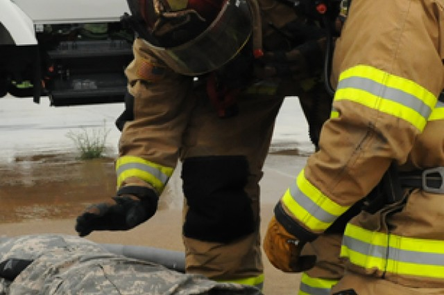 First responders from the Directorate of Emergency Services, Fire and Emergency Services, assess the situation and provide aid to a simulated injury during the airfield exercise May 12.