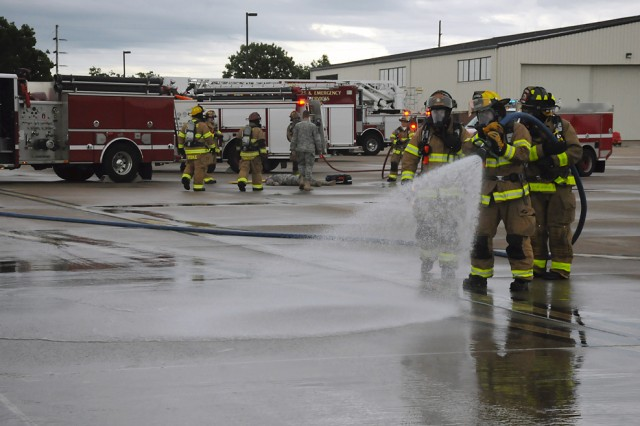 Fire fighters with the Fort Leonard Wood Directorate of Emergency Services use water in place of suppressive foam to clear a simulated fuel spill, as part of their joint emergency response training drill on Forney Army Airfield May 12.