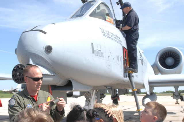 Air National Guard Lt. Col. Michael Sadler allows children to touch dummy rounds used for the A-10 Thunderbolt Attack plane Friday at Airfield Appreciation Day at Forney Field.