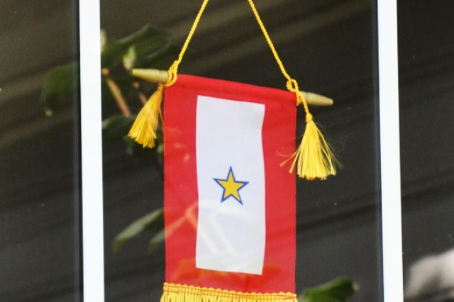 A Service Flag with a blue star covered by a gold star in the window of a home signifies that a family member in that household died in service to our Nation. (U.S. Army photo.)