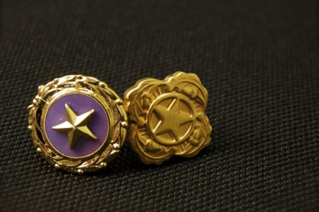 Lapel pins like these indicate the wearer has an immediate family member who was killed in combat (left) or died in service, but not in theater (right). (U.S. Army photo.)