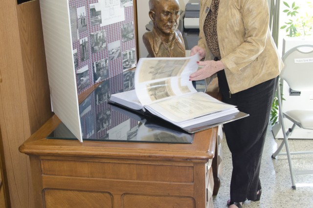 Robert F. Sink's only surviving daughter, Robin Sink McLelland, flips through a collection of vintage photographs Friday taken 50 years ago at the Robert F. Sink Memorial Library groundbreaking ceremony. McLelland, awash in nostalgia, pointed out photos that included her and her Family while standing next to her father's work desk.