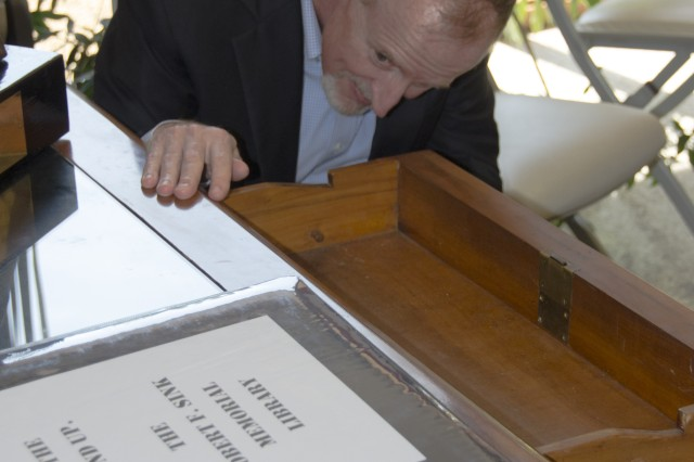 Jonathan Hunter, deputy to the garrison commander, marvels at the Brazilian mahogany desk Lt. Gen. Robert F. Sink used for years during his command across the world. Sink's daughter, Robin McLelland, donated the desk to the Robert F. Sink Memorial Library, during the library's 50th anniversary celebration Friday, hoping patrons would enjoy using it.