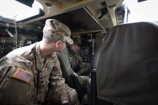 Sgt. Hua Wen, a 29E Electronic Warfare Specialist, from 1st Battalion, 3rd Aviation Regiment, 12th Combat Aviation Brigade and Private Ndifon Leofinn, from JägerBattalion 291, discuss the operation of the RASIT radar system mounted on a German Fox transport vehicle near Fritzlar, Germany, May 19, 2016.  Strong Punch is an exercise laboratory in which German and American aviators can evaluate and refine the effectiveness of their current tactics, techniques and procedures (TTP's) in a threat environment that consists of real world, modern electronic warfare platforms (EW) and reconnaissance surveillance equipment.