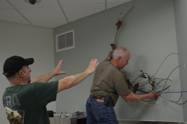 "Bill Kleinedler and his father-in-law John Tripp hang the new sculpture ""Wind Song"" in the dining room May 13 at Brooke Army Medical Center."