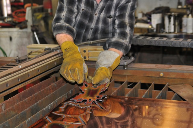 """Bill Kleinedler cuts out leaves made from copper for the """"Wind Song"""" sculpture, which will hang in the newly renovated dining room at Brooke Army Medical Center."""