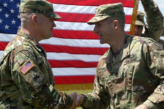 The Sergeant Major of the Army Daniel A. Dailey congratulates Sgt. Kevin LaRose on his reenlistment during a ceremony on Camp Bondsteel, Kosovo, May 18. U.S. and NATO forces have contributed to the United Nations-mandated peacekeeping mission in Kosovo since June 1999.
