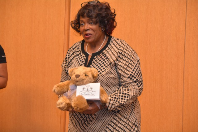 Barbara Johnson, a bereavement nurse on 5 East, holds one of the Comfort Cubs they received as part of their welfare donation May 13 at the BAMC Welfare Recognition Ceremony in the auditorium.