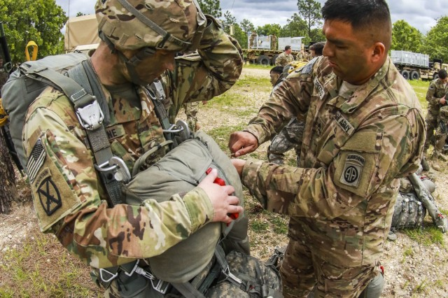 Staff Sgt. Manuel Orozco, indirect fire infantryman, 5th Squadron, 73rd Cavalry Regiment, 3rd Brigade Combat Team, assists Staff Sgt. Everet Enstine, an infantryman from the same unit in donning his parachute during the Little Group of Paratroopers event of All American Week 2016,Fort Bragg, N.C. May 23. The LGOP event tested the paratroopers on their essential task list with events such as rigging their equipment, readying their equipment for service, and a layout of all required equipment. (U.S. Army photo by Staff Sgt. Christopher Freeman/ 82nd CAB PAO)