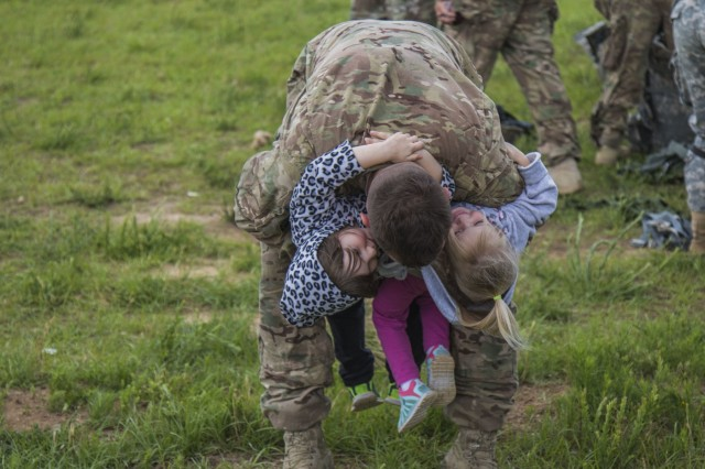 Spc. Greg Rino, wheeled vehicle mechanic, 2nd Battalion, 505th Parachute Infantry Regiment, 3rd Brigade Combat Team, hugs his kids following the Little Group of Paratroopers event of All American Week 2016,Fort Bragg, N.C. May 23. The LGOP event tested the paratroopers on their essential task list with events such as rigging their equipment, readying their equipment for service, and a layout of all required equipment. (U.S. Army photo by Staff Sgt. Christopher Freeman/ 82nd CAB PAO)