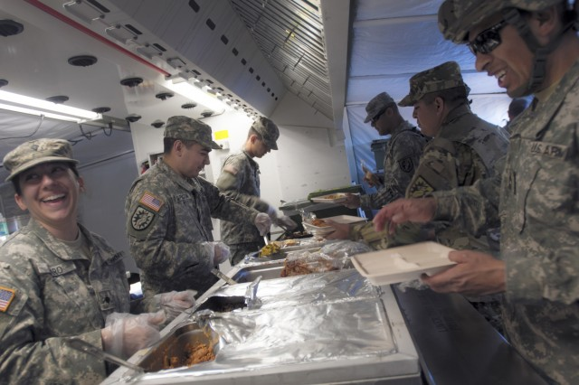 After a long day of erecting tents and establishing operational capabilities, food service specialists from the 224th Sustainment Brigade's Headquarters Company served a hot meal to worn down troops from their Containerized Kitchen unit at Camp Roberts, May 15. The brigade arrived on site last week in support of the California Army National Guard's 2016 annual training event. (U.S. Army Photo by Staff Sgt. Melissa Wood/RELEASED)
