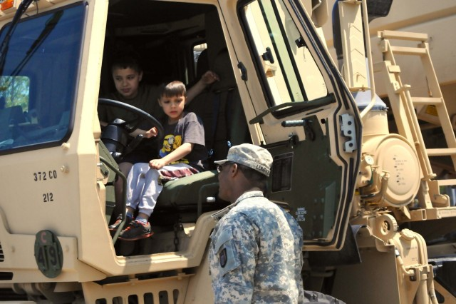 A child tries out an Army M1142 Tactical Fire Fighting Truck belonging to the 482nd Engineer Detachment (Firefighting) during the Milwaukee Armed Forces day event in Milwaukee, May 21. (Photo by Spc. Brianna Saville)