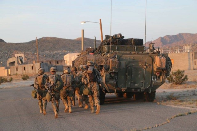 Soldiers assigned to 1st Battalion, 23rd Infantry Regiment, 1-2 Stryker Brigade Combat Team, take cover behind a Stryker, while clearing a city during Decisive Action Rotation 16-06 at the National Training Center in Fort Irwin, Calif., May 11, 2016. The training focused on the 1-2 SBCT combating a near-peer enemy and smaller militant groups in a foreign country.