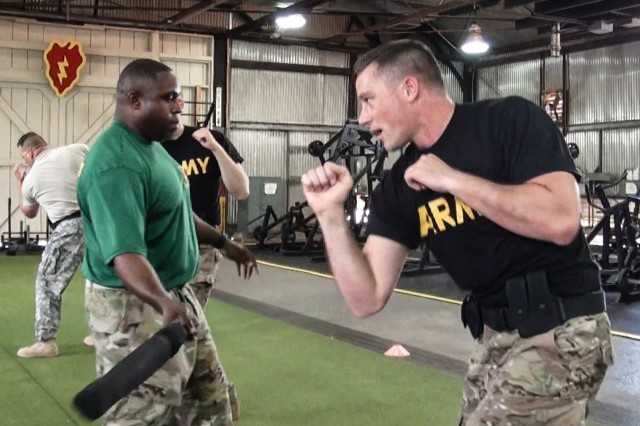 Army Sgt. Ashley W. Barnes (right) serving as the acting squad leader for the 414th Military Police (MP) Company headquartered in Joplin, Missouri, prepares to block a blow delivered by Army Staff Sgt. Jean-Hubert Cadet (left), serving as a law enforcement noncommissioned officer-in-charge for the Directorate of Emergency Services, U.S. Army Garrison-Hawaii, during a non-lethal weapons and tactics course conducted May 19, 2016, at Schofield Barracks, Hawaii.