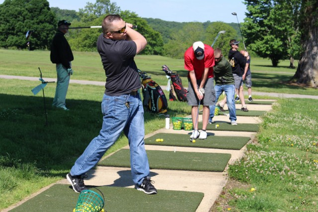 Service members practice at the driving range during a session of free golf lessons at PVGC.