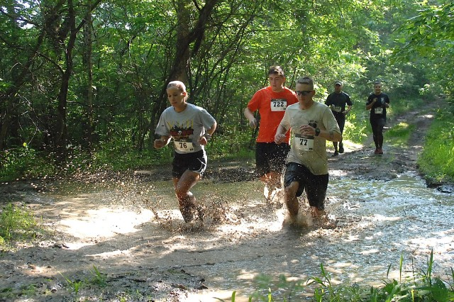 Kendra Howard (76) and Jamie Howard (77) lead a group of runners across one of three mud pits near the halfway point of the 2016 Volkslauf Mud Run. The race was held Saturday starting near Happy Hollow Recreation Area.