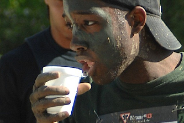 Quadir Muhammad gets a drink at a water station 2 miles from the finish.