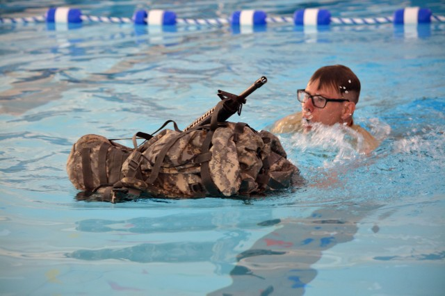 Sgt. David Pearson, headquarters, Tank-automotive and Armaments Command Life Cycle Management Command, swims with a ruck sack and rifle at the Best Warrior Competition mystery event Ft. McCoy, Wisconsin, May 24. (Photo by Mike Bassett, ASC Public Affairs)
