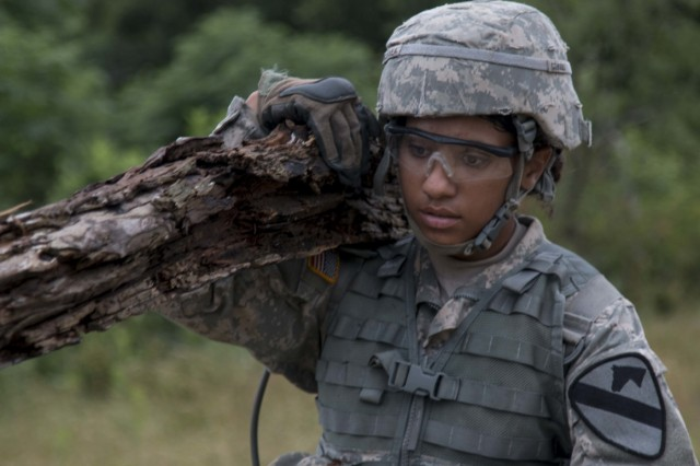 Pfc. Chrisslene Tialavea, a combat engineer assigned with Company B, 3rd Engineer Battalion, 3rd Armored Brigade Combat Team, 1st Cavalry Division, hauls one end of a log to place between rows of concertina wire. The Soldiers spent a week in the field qualifying in basic engineer tasks, including emplacing obstacles and digging ditches. (U.S. Army photo by Staff Sgt. Leah R. Kilpatrick, 3rd Armored Brigade Combat Team Public Affairs Office (released)