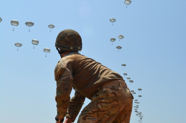 "British Army Paratrooper Lance Cpl. David Maclellan with the 216th Parachute Signal Squadron picks up his parachute after jumping onto Sicily Drop Zone during the All American Week 2016 Airborne Review on Fort Bragg, N.C., May 26. The Airborne Review is the culminating event of All American Week 2016, which is an opportunity for Paratroopers past and present to celebrate being members of the All American Division. This year's All American Week Theme was, ""Tomorrow's Force, Today!"""
