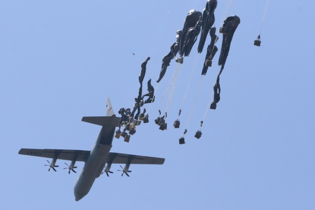 "A C-130 Hercules unloads an equipment heavy drop at the Aiborne Review during All American Week at Sicily Drop Zone, Fort Bragg, N.C., May 26, 2016. The Airborne Review is the culminating event of All American Week 2016, which is an opportunity for Paratroopers, past and present, to celebrate being memebers of the All American Division. This year's All American Week theme is ""Tomorrow's Force, Today!"""