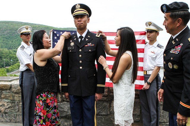 Class of 2016 Tuan Le receives his commissioning bars from his mom (left) and his significant other while his uncle, Maj. Ben Nguyen, looks on May 21 after the U.S. Military Academy Graduation Ceremony (U.S. Army photo by Kathy Eastwood, USMA West Point Public Affairs/released.)
