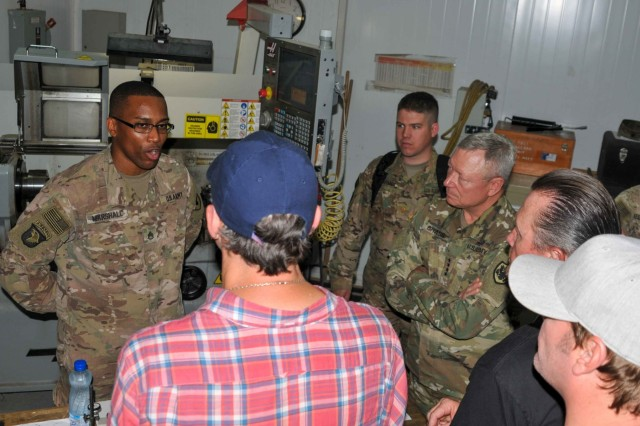 Staff Sgt. Robert Marshall (left), a machinist with 1109th Theatre Aviation Sustainment Maintenance Group, talks to Matthew Lillard (blue hat), Gen. Frank Grass (center), the chief of the National Guard Bureau, Robert Patrick (black shirt) and Jerrod Neimann (white hat) about helicopter parts he created on Camp Arifjan, Kuwait, May 18, 2016. This visit was part of the USO May Madness Tour. (U.S. Army photo by Sgt. David N. Beckstrom, 19th Public Affairs Detachment, U.S. Army Central)