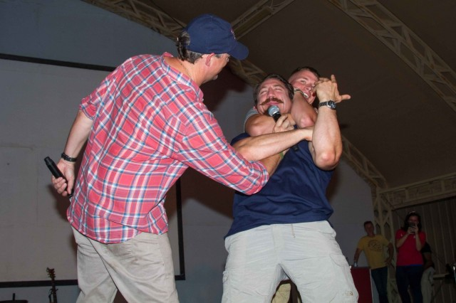 Matthew Lillard (left), actor, holds a microphone for Sgt. 1st Class Timothy Kennedy, a National Guardsman with the 19th Special Forces Group and a mixed martial artist with the Ultimate Fighting Championship, while he instructs Spc. Logan Kelly, a carpenter with 1194th Engineer Company, 682nd Engineer Battalion, on how to properly preform a rear naked choke during the USO May Madness Tour on Camp Arifjan, Kuwait, May 18, 2016. The celebreties on the tour said they wanted to repay Servicemembers for their sacrifice and dedication to America. (U.S. Army photo by Sgt. David N. Beckstrom, 19th Public Affairs Detachment, U.S. Army Central)