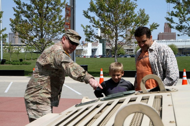 Major Harold Aprill, the executive officer for the 3rd Battalion, 399th Regiment, shows a young boy and his father the durability of a Humvee during the 2016 Armed Forces Day celebration at the Milwaukee Harley-Davidson Museum, May 21, 2016.  Aprill, who is also a member of the Milwaukee Armed Services Committee, helped organize the event which capped off an entire week of activities for Milwaukee's Armed Forces Week.   Aprill and reservists from the 3/399th, as well as volunteers from the other branches, helped raise military awareness by displaying military vehicles and explaining to civilians their current role in supporting ongoing military efforts around the world. Service members past and present mingled with the crowd throughout the day, a highlight of which was the 13th annual Support the Troops Ride which featured over 300 motorcycle riders.