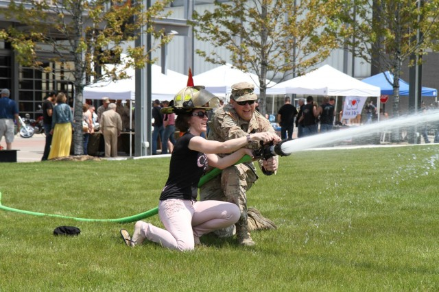 Major Harold Aprill, the executive officer for the 3rd Battalion, 399th Regiment, shows Becca Osmak of St. Francis, Wis. how to properly control the water pressure from a fire hose during the 2016 Armed Forces Day celebration at the Milwaukee Harley-Davidson Museum, May 21, 2016.  Aprill, who is also a member of the Milwaukee Armed Services Committee, helped organize the event which capped off an entire week of activities for Milwaukee's Armed Forces Week.   Aprill and reservists from the 3/399th, as well as volunteers from the other branches, helped raise military awareness by displaying military vehicles and explaining to civilians their current role in supporting ongoing military efforts around the world. Service members past and present mingled with the crowd throughout the day, a highlight of which was the 13th annual Support the Troops Ride which featured over 300 motorcycle riders.