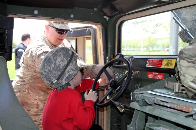 Major Harold Aprill, the executive officer for the 3rd Battalion, 399th Regiment, shows Max Osmak of St. Francis, Wis. how to start a Humvee during the 2016 Armed Forces Day celebration at the Milwaukee Harley-Davidson Museum, May 21, 2016.  Aprill, who is also a member of the Milwaukee Armed Services Committee, helped organize the event which capped off an entire week of activities for Milwaukee's Armed Forces Week.   Aprill and reservists from the 3/399th, as well as volunteers from the other branches, helped raise military awareness by displaying military vehicles and explaining to civilians their current role in supporting ongoing military efforts around the world. Service members past and present mingled with the crowd throughout the day, a highlight of which was the 13th annual Support the Troops Ride which featured over 300 motorcycle riders.