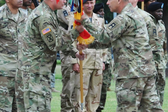 FORT HOOD, TEXAS -- Maj. Gen. Jeffrey N. Colt (right), commander of Division West, First Army, passes the guidon to the incoming commander of the 120th Infantry Brigade, Col. Brian Payne, as Payne assumes command of the brigade during a ceremony held on Cameron Field May 25. Payne is taking the reins from Col. Daniel S. Hurlbut, who commanded the brigade for two years. (US Army photo by Sgt. 1st Class Garrett N. Ralston)