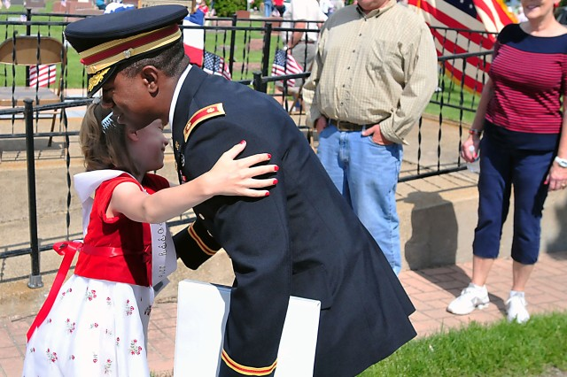 A young attendee gives a hug to Maj. Lanelle Pickett Jr. of ASC's Distribution Management Center at the Galva Cemetery in Illinois following the Memorial Day ceremony May 30. Pickett served as the keynote speaker. (Photo by Jon Micheal Connor, ASC Public Affairs)