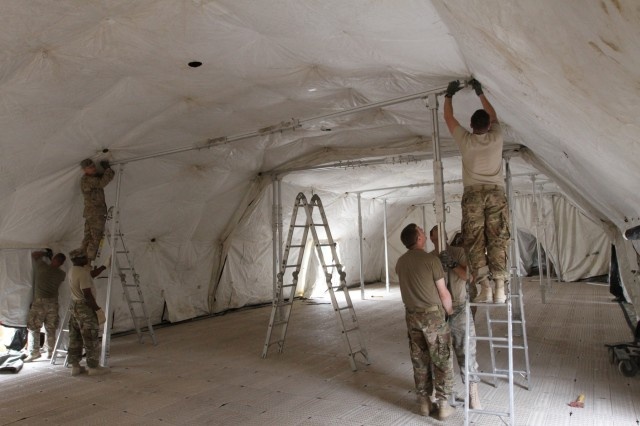 Soldiers assigned to U.S. Army Central construct the interior bracing for the deployable rapid assembly shelter, also known as DRASH, before the annual exercise called Eager Lion. Eager Lion is a multinational exercise held between the U.S. Army and Jordanian Armed Forces where relationships are deployed and interoperability is practiced. (U.S. Army photo by Sgt. Victor Everhart Jr.)