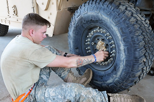 Rotating units must turn in vehicles issued to them by LRC-Polk in fully mission capable condition. Here a Soldier works on a Humvee wheel prior to turning in. (Photo by Jon Micheal Connor, ASC Public Affairs)
