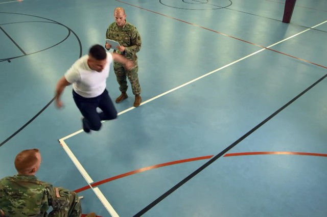 "Soldiers administer the ""standing long jump"" portion of the Occupational Physical Assessment Test to potential recruits during an OPAT pilot program."
