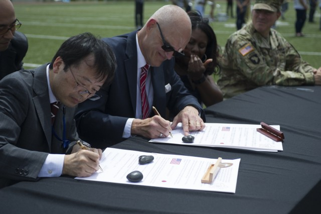 Shinichi Imai, principal of Ebina High School, and Gregg Mowen, Ed.D., principal of Zama American High School, sign a charter which forges a new relationship between the two schools May 26 at ZAHS's activity field. (U.S. Army photo by Alia Naffouj)