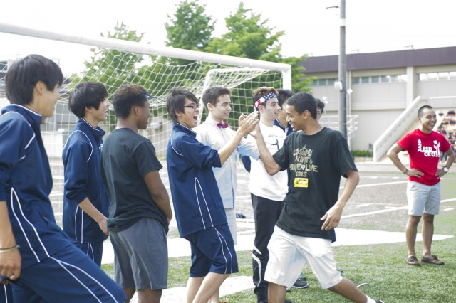 EHS students welcome their ZAHS student teammate as they pick teams to play soccer during Field Day held at ZAHS May 26, where the EHS principal and the ZAHS principal signed a charter forging a new partnership between the two schools. (U.S. Army photo by Alia Naffouj)