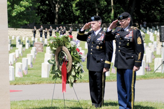 """Maj. Gen. Wayne W. Grigsby Jr., 1st Infantry Division and Fort Riley commanding general, left, and Command Sgt. Maj. Jonathan D. Stephens, 1st Infantry Division Artillery, right, salute the memorial wreath May 30 during the Memorial Day ceremony at Fort Riley. The wreath bares the inscription, """"lest we forget."""""""