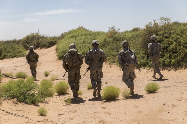 Soldiers assigned to Company C, 3rd Battalion, 41st Infantry Regiment, 1st Brigade Combat Team, 1st Armored Division, patrol the area during Hustler Trough III May 24 at the Orogrande Range Complex, N.M.