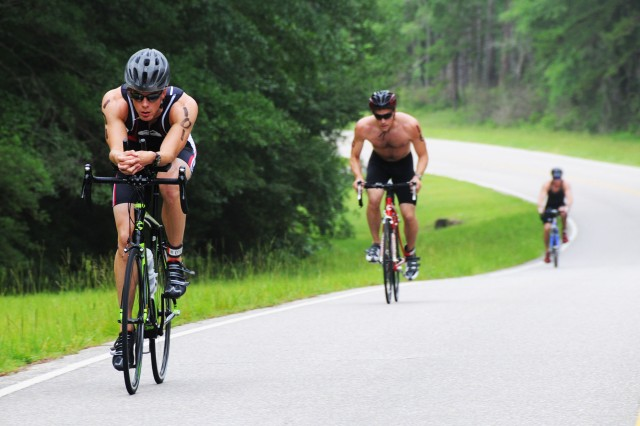 Erik Moore, triathlon competitor, bikes ahead of two other competitors during the 10.6-mile bike ride of last year's triathlon.