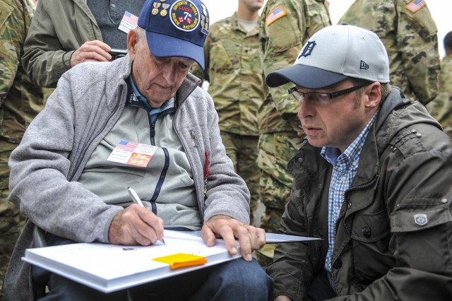 Cliff Goodall, a World War II veteran, signs an autograph after a memorial ceremony June 4, 2016, in Angoville-au-Plain, France. The memorial ceremony was in honor of Kenneth Moore and Robert Wright, medics with the 101st Airborne Division during World War II, who provided medical care to allies and enemies alike at the Angoville-au-Plain church in June 1944.