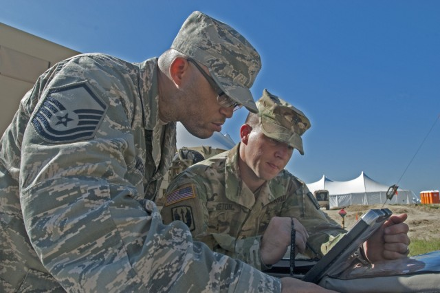 Master Sgt. Aaron Z. McKenzie, 225 Air Control Squadron, an element of the Mississippi National Guard, radio frequency transmitter, explains to Sgt. Shawn Keeton, 102d Public Affairs Detachment, broadcaster, how to setup frequencies to transmit news for the assigned missions, during the Multi-echelon Integrated Brigade Training (MiBT) exercise, June 7, 2016, at Fort Hood, Texas. A MiBT is a multicomponent training event that sustains readiness of reserve and active components in accordance with the U.S. Army's Total Force policy.