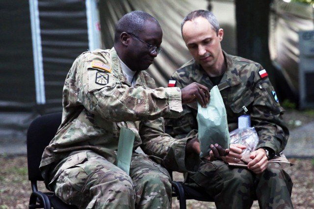 "Lt. Col. Paul Powell from the U.S. Army Europe G6 shares an MRE meal with a Polish CIS officer during Exercise Anakonda 2016 June 6 at the National Defense University in Warsaw, Poland. ""This is important for relationships and for enabling the Alliance. Relationships are built over time, and this exercise is just another step in the improving of our relationships and enabling the Alliance,"" said Col. Jimmy L. Hall Jr., commander of 5th Signal Command (Theater) and the U.S. Army Europe chief information officer/G6."