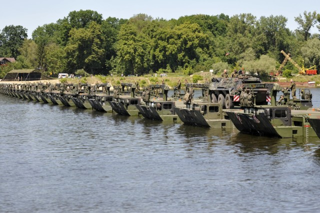A U.K. military vehicle quickly crosses the makeshift bridge that closed the gap in the Vistula River in Chelmno, Poland June 7 as part of a joint exercise in Exercise Anakonda 2016. The bridge was created by connect 34 U.K. and German Amphibioius Rigs together, which was able to support 200 U.S. Army vehicles crossing.