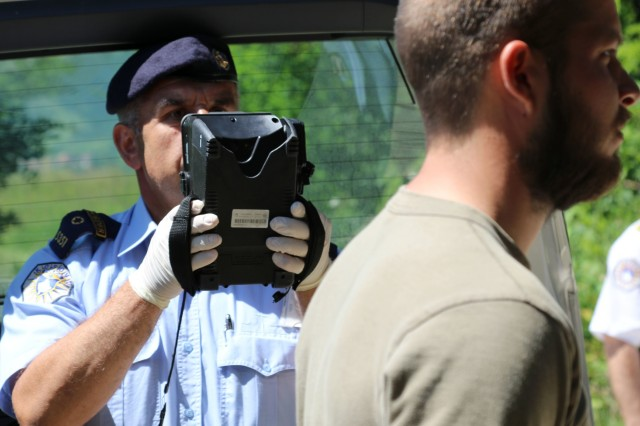 A member of the Kosovo Border Police photographically documents the entry of a [migrant] trying to cross into Kosovo during Operation Silver Saber June 3.  (U.S. Army photo by: Staff Sgt. Thomas Duval, Multinational Battle Group-East Public Affairs)